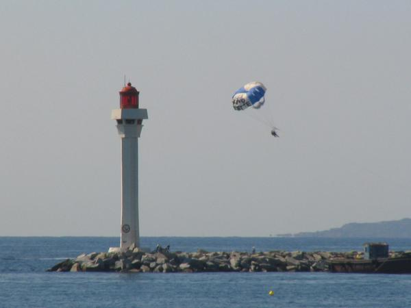 Parachuta behind the beacon of Cannes Two hang on the parachute here just near behind the beacon of Cannes floats.