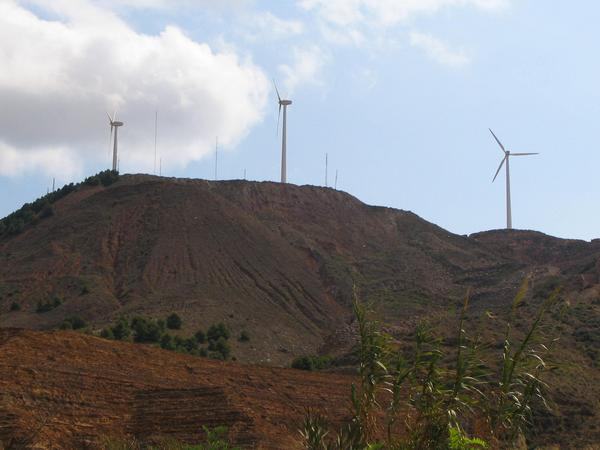 Wind power plant La union Murcia Spain Already in visibility ruin of the old wind mill: modern wind power plants on the mountains of the abandoned silver mine La union.