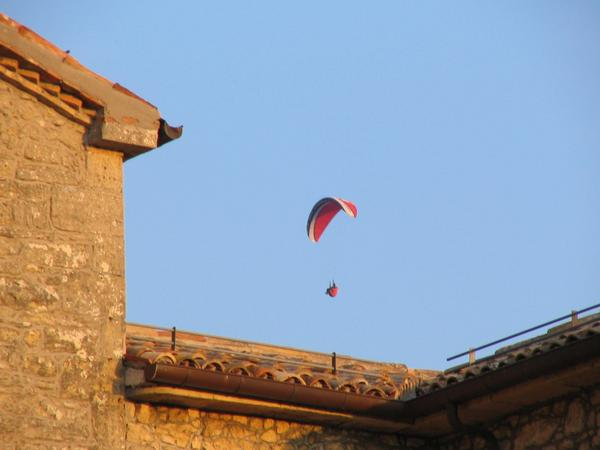 Paraglider over the roofs of San Marino The thermic at the step Titano montains seems to be strong enough, to climb higher than the starting point.