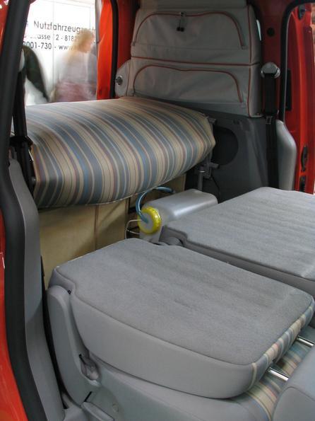 La cama plegable de VW Caddy Los aseentos traseros estan plegados hacia delante. Detras esta la cocina Vanessa con la botella de agua. Arriba el colhon de la cama plegable.