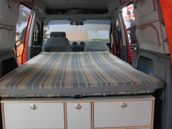 Caravana VW Caddy Los asientos traseros se doblan hacia adelante y sirven como soporte para el colchon. Con los cinturones de seguridad se fija bien el colchon.