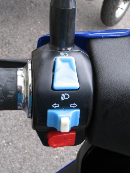 Left grip on the electric scooter E-Max S Up the switch for dipped down and main light. In the middle sliding switch for the blinker. The white button is to switch of the blinker. The red button below is the hooter.