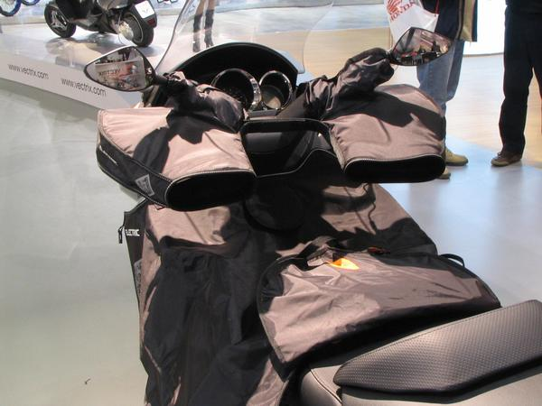 Gloves to drive motorcycle in winter On Vectrix on the booth had been special equipped for driving in winter. Gloves are mounted on the grips, the driver puts his hands into the gloves to drive.