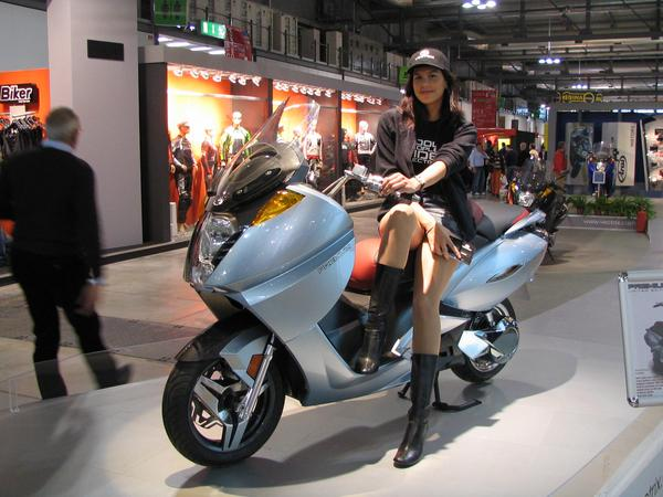 Beautifull girls on motorcycles Like everywhere on the EICMA belong beautiful girls on motorcycles to this event. Here on an electric Vectrix maxi scooter.