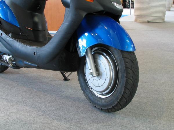 Ciclomotor con motor en la rueda delantera El motor de combustion interna tiene la propulsion en  la rueda trasera. En la rueda delantera hay un motor electrico. El ciclomotor hibrido puede pasar al modo electrico con traccion delantera, como si fuera una bici electrica.