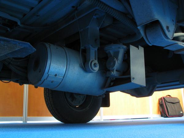 El motor del pequeno electrico van Fotografia de debajo del minibus en la parte del eje trasero. La conexion del motor electrico con el pivote del eje trasero.