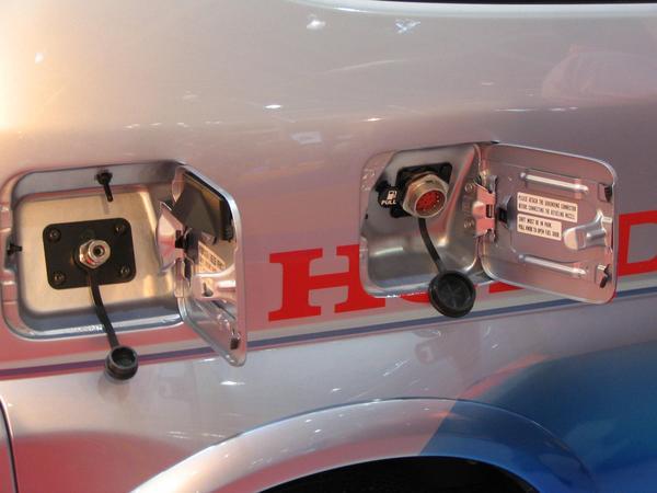 Honda FCX hydrogen deposito Para abrir el tapon izquierdo para llenar el deposito con gas, primero hace falta conectar el cable de tierra al tapon derecho.