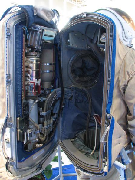 Partea din spate a unui costum rusesc de cosmonaut. Costumul de cosmonaut este deschis pentru a se putea intra in el. In spate se poate vedea tot ansamblul de aparate cu care este dotat.