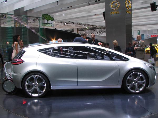 Opel Flextreme side view PHEV Plug-in hybrid car. In the rear are the open Segway garage visivle.
