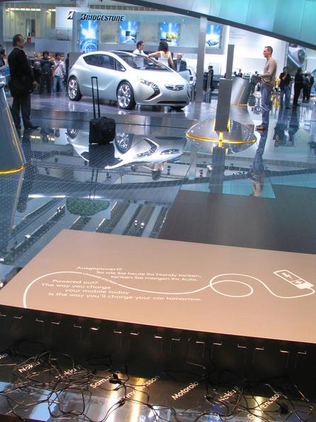 Tomorrow we will charge our cars like our mobiles On the IAA 2007 booth of Opel is near the Flextreme a couch and a desk with plugs to recharge mobiles. On the desk is written: