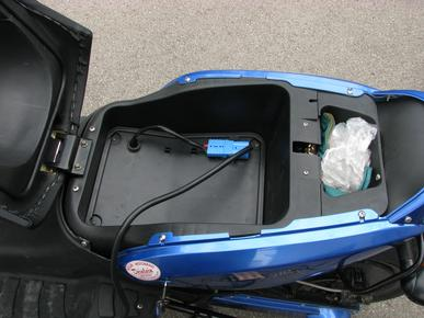 Charger e-max-110s The 1300 Watt charger with metall case just fits in the charger locker below the seat. The helmet locker is here sized down to a charger locker. Picture 1