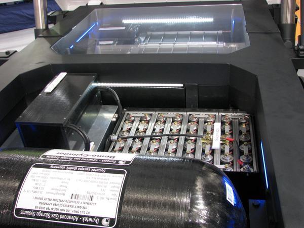 Por que hacerlo simple cuando se puede complicar. Debajo de la plataforma hay 2 depositos de hidrogeno bajo presion, en la foto se ve solo 1, una bateria , condensadores y un acumulador.