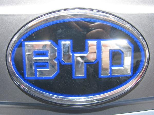 Brand name BYD Close up from the BYD logo in front of the e6 electric car.