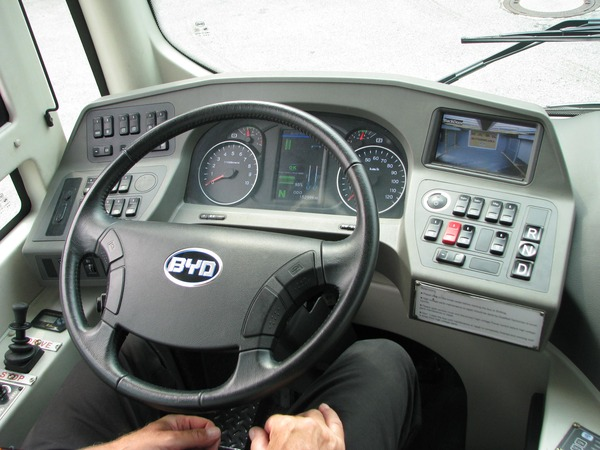 Dashboard BYD electric bus The workplace for the driver. The screen can be switched betwee rear view and the middle entrance. In the middle is the battery display about the charging status in percent.
